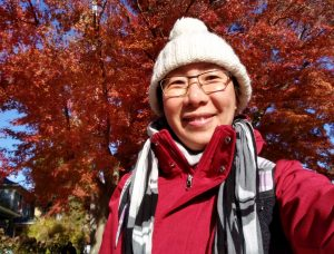 Chinese woman smiling in a beanie and red jacket